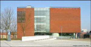 ARoS - den kubiske bygning, der måler 52 x 52 meter og har en højde på ca. 50 meter er tegnet af Schmidt Hammer Lassen Architects. Den er inspireret af Dantes Den Guddommelige Komedie; kælderen er helvede og tagrummet er himmelen. Indviet 07.april 2004