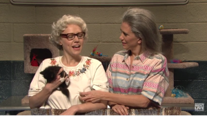 Barbara DeDrew (Kate McKinnon) and Furonica (Kristen Wiig) show off the cats available for adoption during the Thanksgiving Catacopia giveaway.