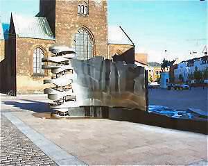 Elisabeth Toubro - Store Torv Aarhus Torvenes Brøndsløjfe (Vanddragen) Årstal : 2003 Materialer : rustfrit stål, sort diabas, støbejern H-L : 3,7 m, 19 m Brønddæksel : 3,2 m